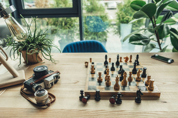 Creative workplace concept with old retro camera, chess board and chess pieces