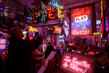 "A visitor photographs a neon sign that reads Let's Play Doctors and Nurses"" in God's Own Junkyard gallery and cafe in London"