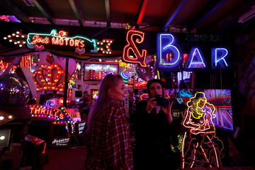 People take pictures of neon signs and artworks in God's Own Junkyard gallery and cafe in London