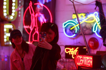 Tourists pose for pictures as they take selfies in God's Own Junkyard gallery and cafe in London