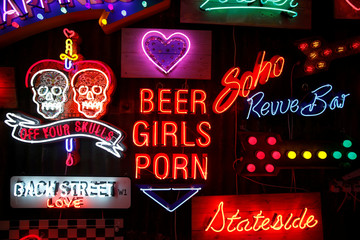 Neon signs that read 'Off Your Skulls', 'Back Street Love', 'Soho Revue Bar', 'Beer Girls Porn' and 'Stateside' are exhibited in God's Own Junkyard in London