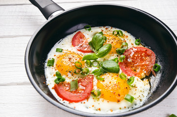Fond de hotte en verre imprimé Ouf Pan of fried eggs with tomatoes, cheese, spring onion, herbs on a white table. White wooden table. Concept of food. Breakfast time. Copy space.