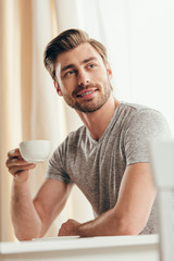Smiling young man holding coffee cup and looking away at home