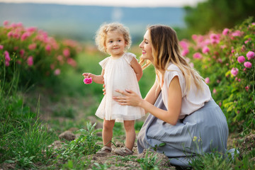 Beautiful child girl with mother are wearing casual clothes sitting in a garden with pink blossom roses