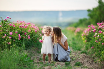 Beautiful young child girl with mother are wearing casual clothes sitting in a garden with pink blossom roses
