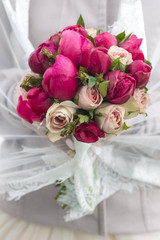 vivid and bright bouquet of different flowers . he holds the bride in a veil.