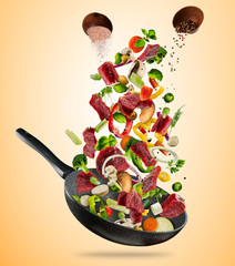 Fresh vegetables and beef meat flying into a pan on brown background