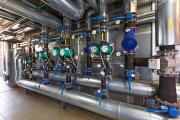 The interior of a modern gas boiler house with pumps, valves, a multitude of sensors and barrels