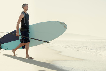 Mid adult man surfer carrying surfboard to sea