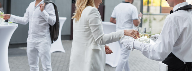 People wearing white enjoying drinks at the outdoor party. Luxury event, body parts.