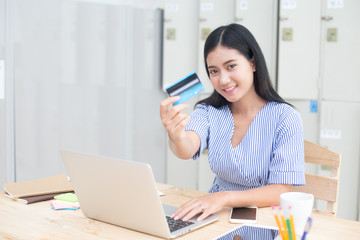 Beautiful asian women using craditcard for shopping online with laptop, online shopping protrait concept.
