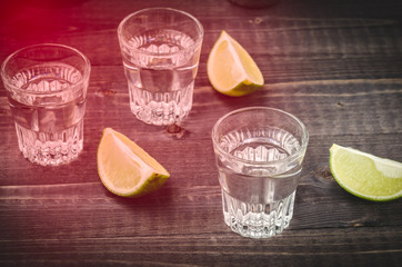 shot glasses and lime on a table/shot glasses with alcohol and a lime with red light