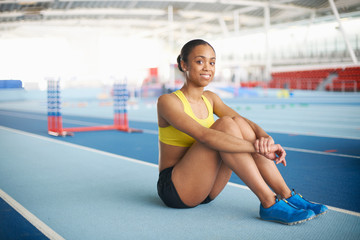 Young female athlete sitting on floor, portrait