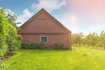 old brick stable shed on lush green meadow under blue sky