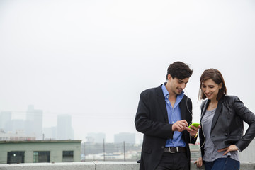 Couple listening to shared earplugs on city rooftop