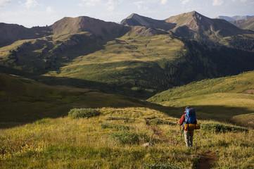 Woman hiking over Frigid Air Pass, West Elk Mountains, Colorado, USA
