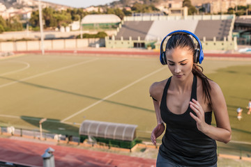 Young woman wearing headphones running, high angle
