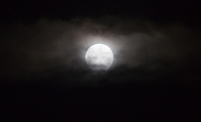 The moon in the haze of the clouds at night