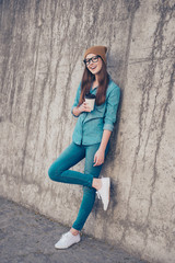 Full length of excited girl, standing near concrete wall outside, smiling, with crossed legs and holding plastic cup with tea, in casual jeans outfit and brown hat, glasses