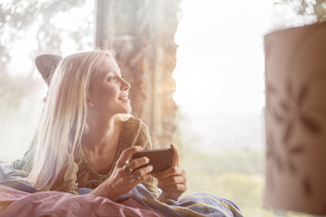 Portrait of smiling young woman lying on bed with cell phone looking through window