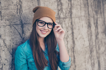 Good morning! Close up of attractive girl, standing near concrete wall outdoors, smiling, fixing her glasses. She is wearing casual jeans outfit and brown hat