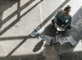 Young woman sitting on concrete floor working on letter templates