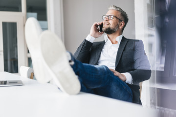 Businessman sitting phoning in office with feet on desk