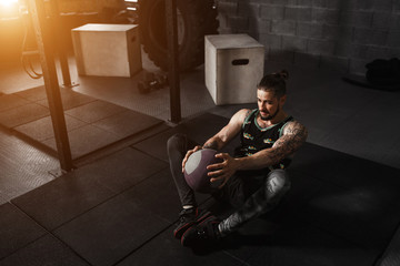 Muscular man doing exercise with medicine ball in crossfit gym