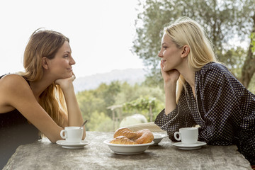 Two smiling face to face friends at breakfast table