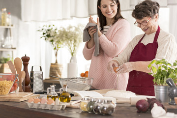 Woman cooking with granddaughter