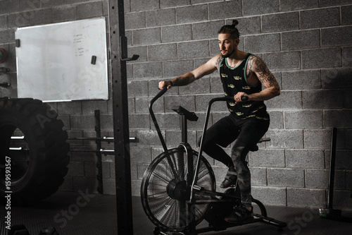 Young Man Using Exercise Bike At The Gym Fitness Male Air For Cardio