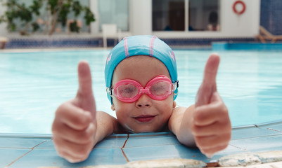 Cute little girl in swimming cap and goggles showing thumbs up in water. Concept of sport and leisure.