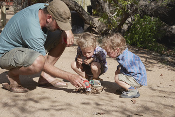 Father and sons trying to start camp fire using magnifying glass and sun, Purros, Kaokoland, Namibia