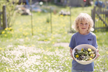 Portrait of young boy holding bowl of garden herbs