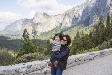 Mature woman carrying granddaughter, Yosemite National Park, California, USA