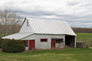 Old wood  barn with red door and metal roof