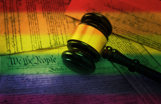Rainbow flag gavel on America's Constitution