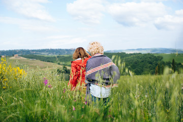 Rear view of two mature women strolling in wheatfield, Tuscany, Italy