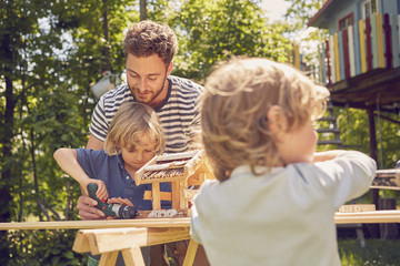 Father and two sons doing woodwork together, outdoors