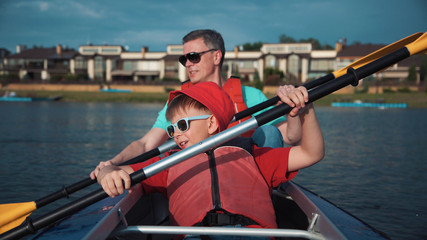 Little boy sitting in kayak with father and rowing.