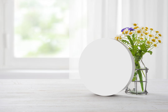 Clear plain banner stand and camomile bouquet on wooden table
