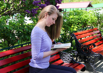 A girl reads a book on a park bench