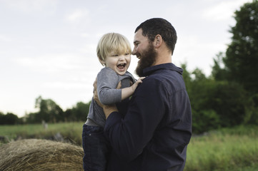 Father holding son, outdoors