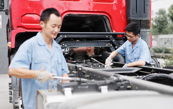 Two male factory workers working on truck at crane factory, China