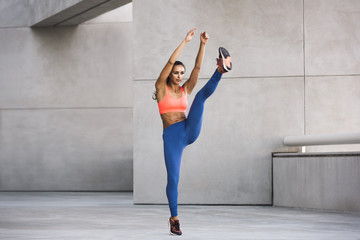 Front view of young woman wearing sports clothing arms raised, leg raised exercising