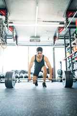 Young fit hispanic man in gym lifting heavy barbell