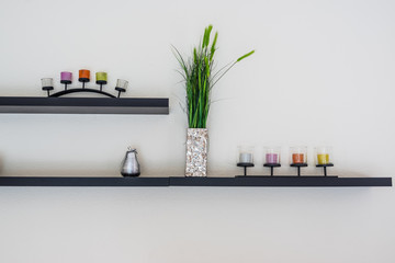 Decorative candle with flower vase on wooden shelf.