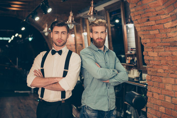 Welcome to barber shop! Red bearded handsome young man in a casual jeans outfit and attractive brunette dressed classy are standing with the crossed hands, looking harsh and fashionable