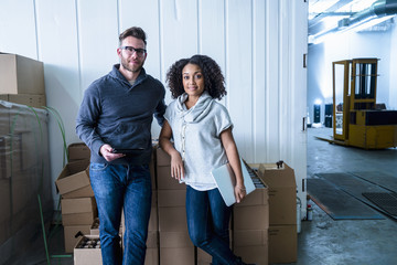 Colleagues in warehouse leaning against cardboard boxes holding digital tablet and laptop looking at camera smiling