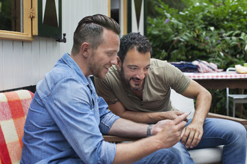 Two men reading smartphone texts on cabin porch